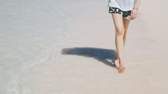 夏の海の波打ち際を歩く女性の足の画像