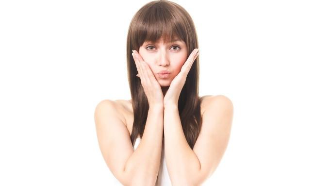 手を頬に添え驚く女性の画像