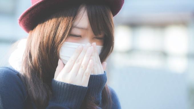 鼻を抑えるマスクをした女性の画像
