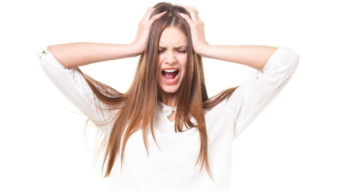 両手で頭を抱えて叫ぶ女性の画像