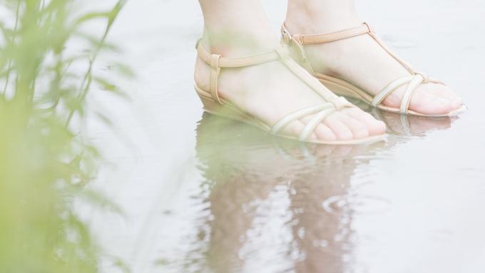 雨に濡れるサンダルを履いた女性の足の画像