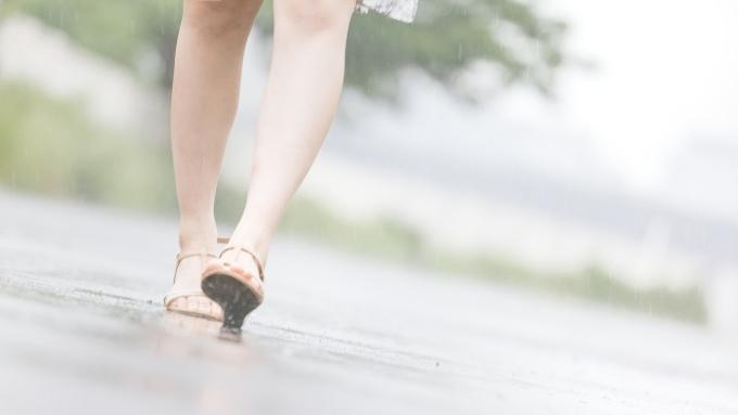 雨の日にサンダルで歩く女性の足の画像