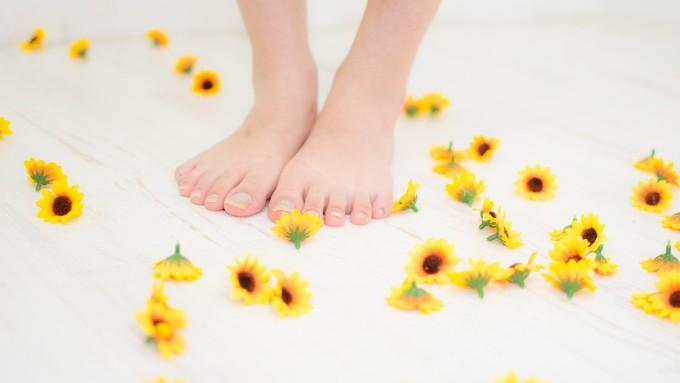 造花の花と女性の素足の画像