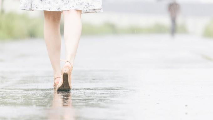 雨の中サンダルで歩く女性の後ろ姿の画像