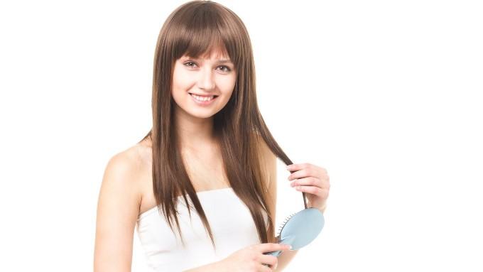 ヘアブラシで髪を梳く女性の画像