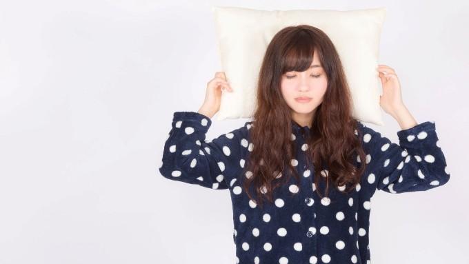 パジャマを着て枕に寝る女性の画像