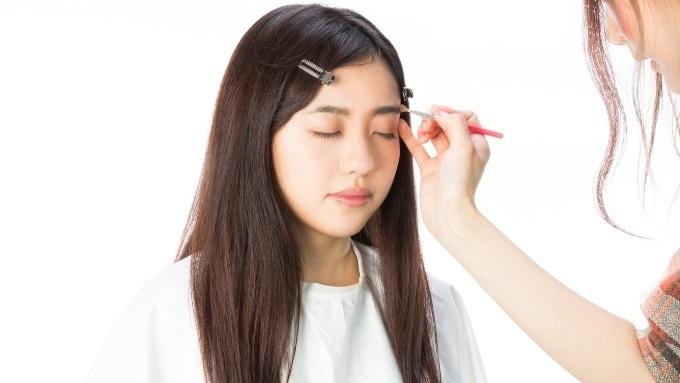 眉毛のお手入れとメイクをする女性の画像
