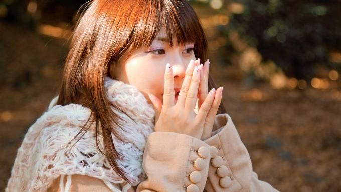 寒さに手を温める女性の画像