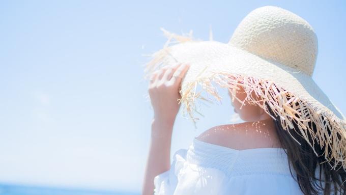 夏の海の日差しに帽子をかぶる女性の画像