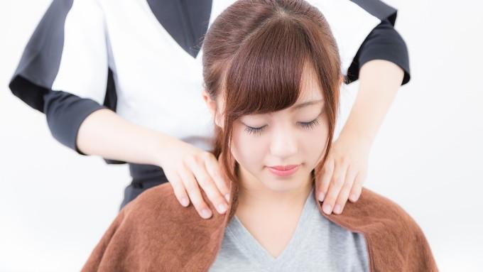 マッサージ師さんに肩を揉まれる女性の画像
