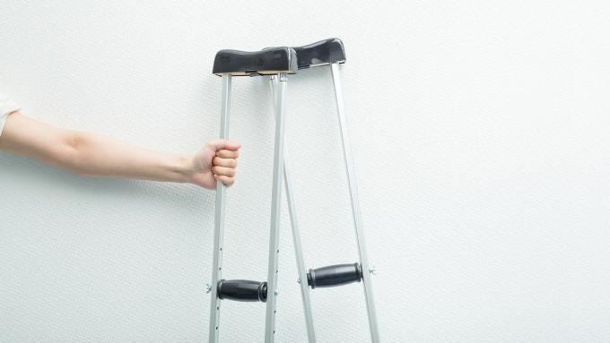 病院と松葉杖と男性の手の画像