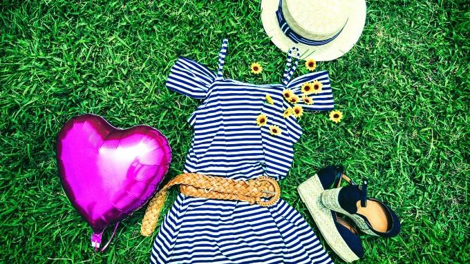 夏服、ワンピースと帽子と靴を芝生に置いた画像