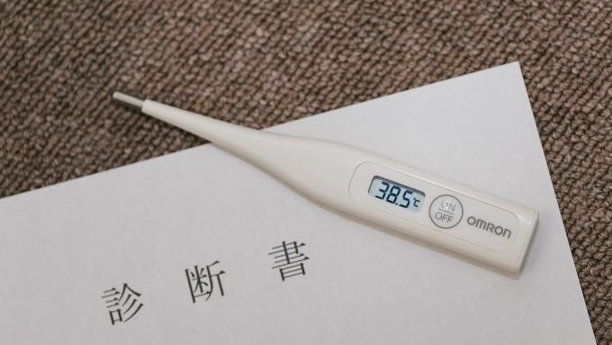 病院の診断書と体温計の画像