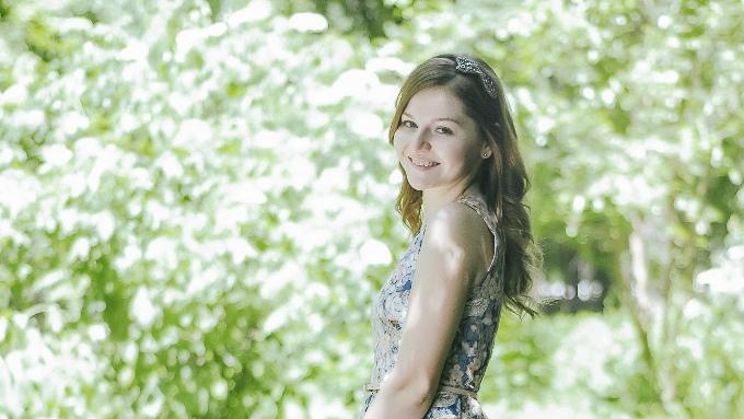 緑に囲まれたきれいなパーマ髪のロシア人女性の画像
