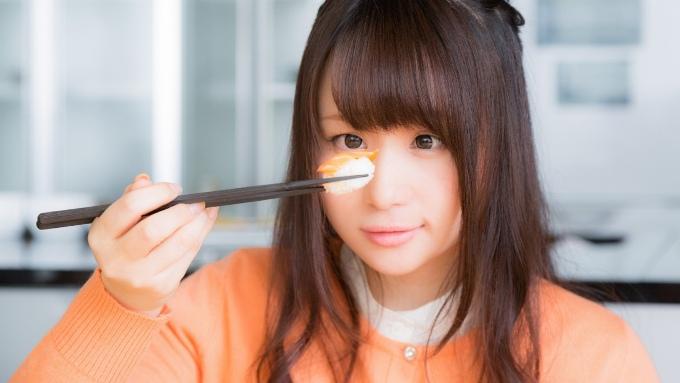 ご飯を箸に取り食べるか悩む女性の画像