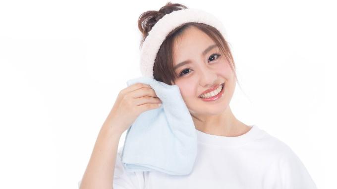タオルを持ち、ヘアバンドを頭に巻く笑顔の女性の画像