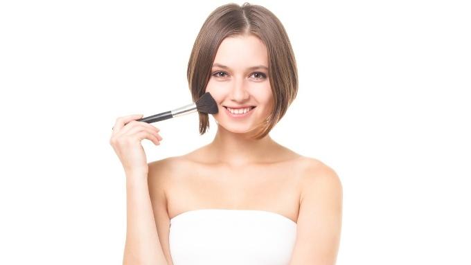 フェイスブラシで顔を塗る女性の画像