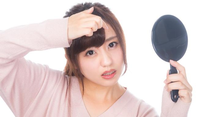 ニキビを気にする手鏡を持った女性の画像