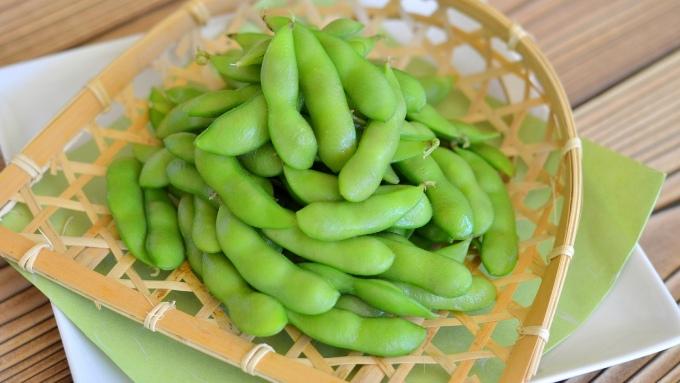 ザルに乗せた茹でた枝豆の画像