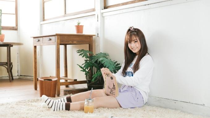 リビングの床に座り読書を楽しむ女性の画像