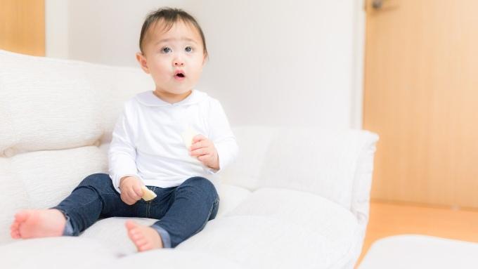 ソファーに座ってTVを夢中で見る赤ちゃんの画像