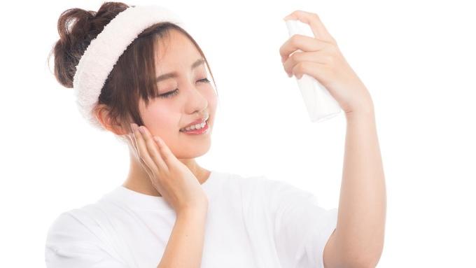 目を閉じて気持ちよさそうに化粧水を顔に付ける女性の画像