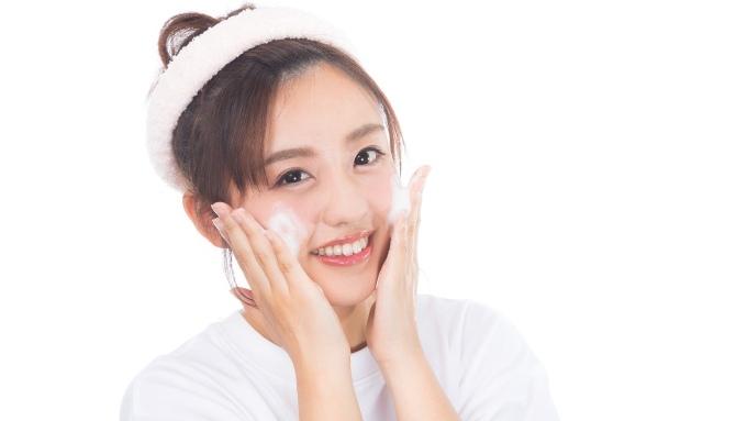 両手に泡をつけ顔を洗う女性の画像
