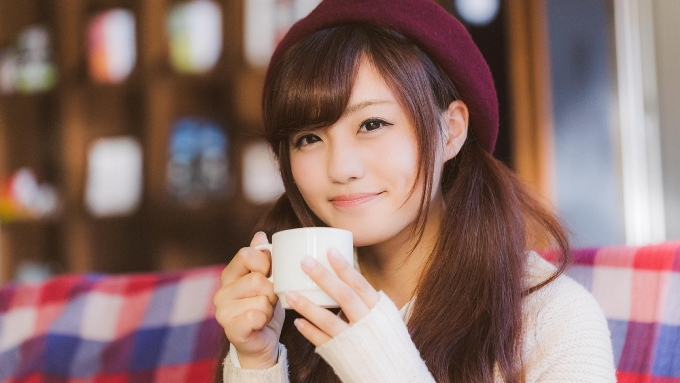 カフェでコップの飲み物を持つ女性の画像