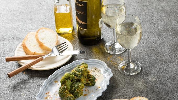 テーブルにグラスワイン、パンにオリーブオイル、おつまみの画像