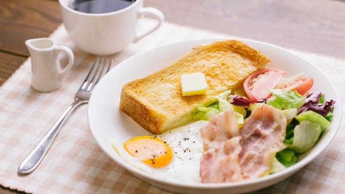 コーヒーとバタートーストにサラダ、べーごんエッグの朝食画像
