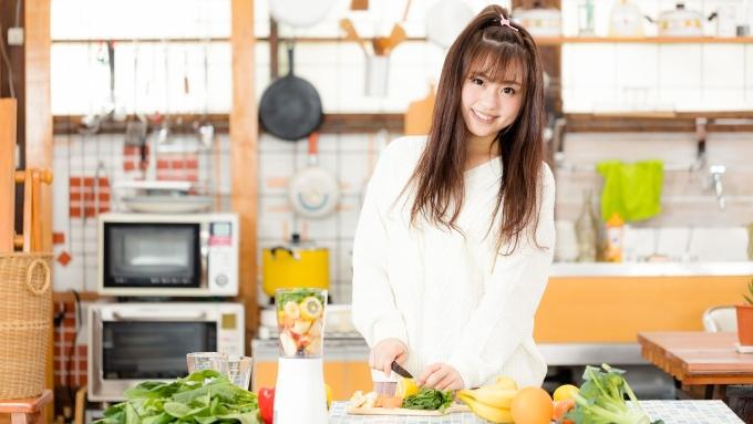 キッチンで料理をする女性の画像