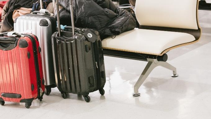 空港の椅子と旅行用トランクの画像