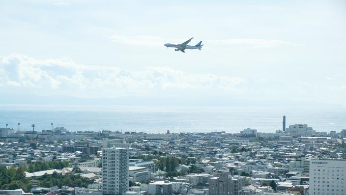 町の上を飛ぶ飛行機の画像